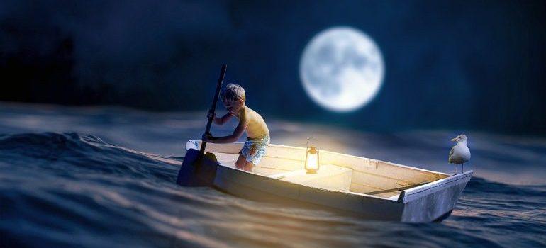 a boy in a ship under a moon