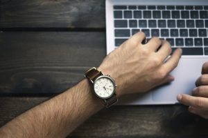 Man with a watch typing