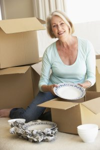 Woman packing dishes while she is downsizing for seniors
