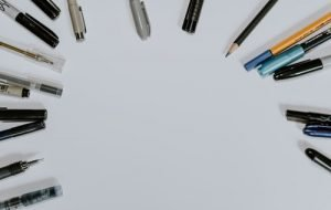 assorted pens on a white surface
