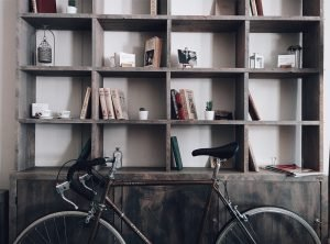 A bicycle in front of a wooden bookshelf.