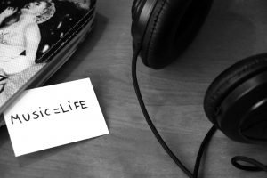 Headphones, phone and a paper that says `music equals life.`