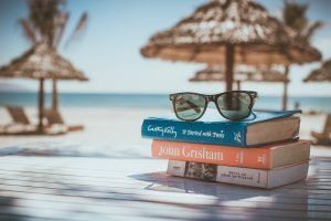 A stack of three books with sunglasses on top of them. Behind them we see the beach and sand.