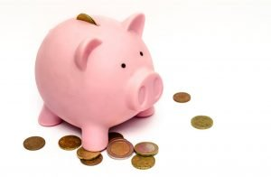 A pink piggy bank with some coins around it.