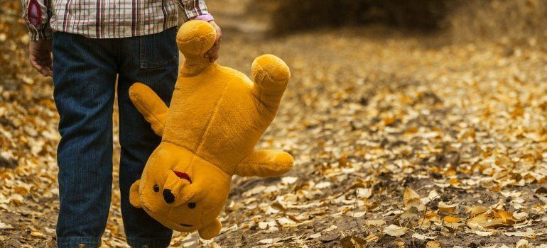 a boy carrying teddy bear