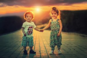 A boy and a girl holding hands.