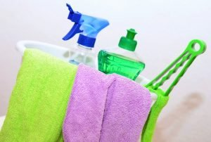 We see a bucket with some cleaning supplies in it, and a green and purple cleaning rags hanging on the front.
