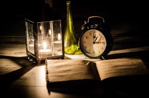 An alarm clock, an open book, a vase and a candle on a table.