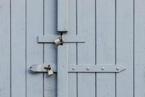 Two padlocks keeping a door closed.