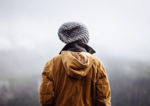 Back view of a man in a jacket and beanie.