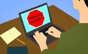 A sketch of a person using a lap top. There is a fraud alert sign on the screen.