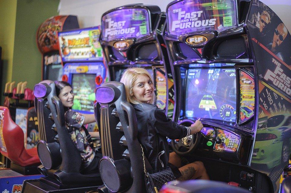 girls playing arcade machin - move arcade machineses