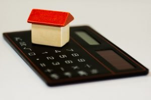 A model of a house placed on a calculator.