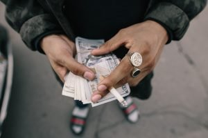 A man with some fancy rings holding a fat stack of cash.