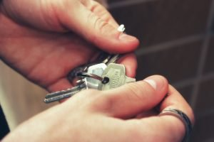 A man holding keys in his hands. It's a good set of keys, and then man is wearing a ring.