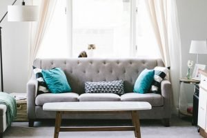 Grey couch with blue pillows in living room.