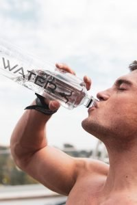 Man following summer moving tips and drinking water