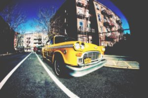 a yellow car on a NYC street