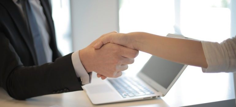 Person in black suit shaking hands and hiring professional movers
