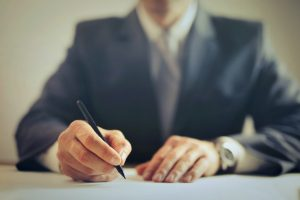 Man signing contract in office