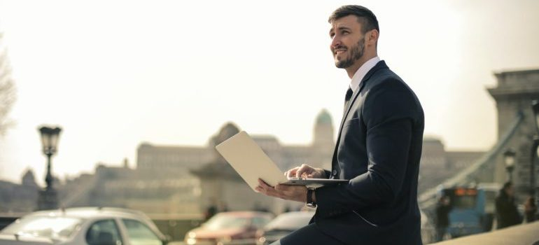 Businessman on laptop in the park