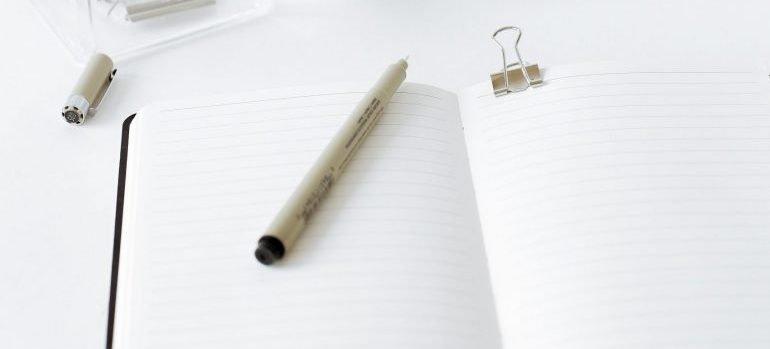notebook, white cup, pencil, pen etc