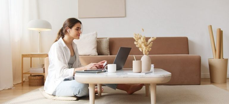 Woman sitting on the floor at the coffee table working on a laptop.