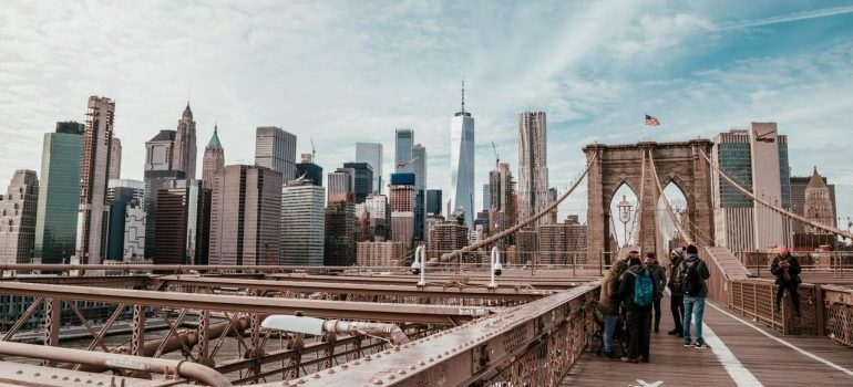 A picture from the Brooklyn bridge of tourists and the city.