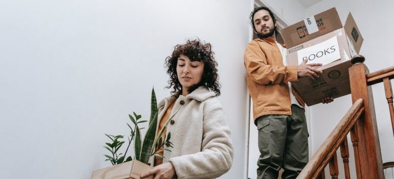 A couple carrying boxes and plants and moving from Brooklyn to Boulder