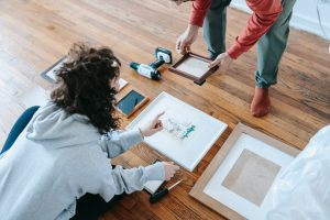 couple packing paintings for moving