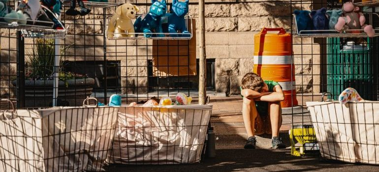 Kid sitting in front of the things he is selling.