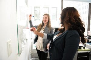 two women writing on the dry erase board