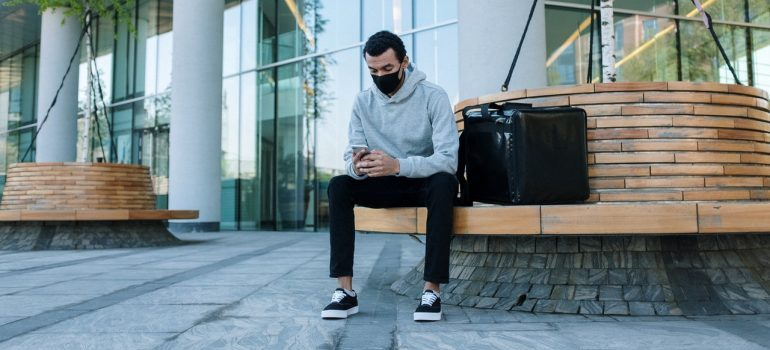 Man sitting on a bench doing one of the simplest tasks when moving, carrying his valuables with him in a big duffel bag