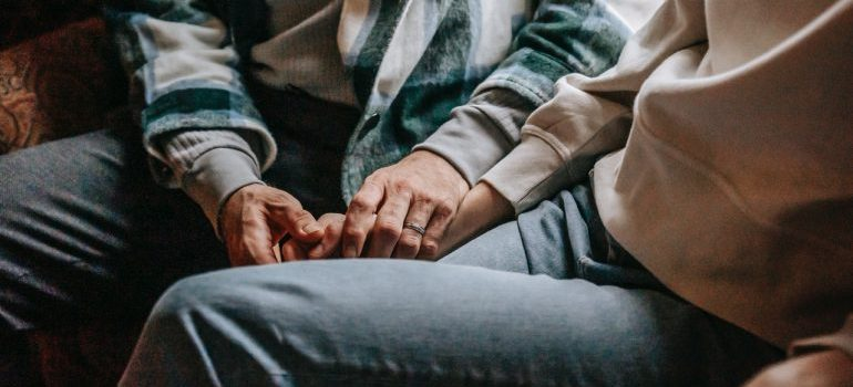 A man holding hands with a woman and providing emotional support to make relocation easier for friends
