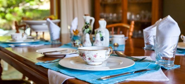 Fine china cups, plates and other utilities on the table.