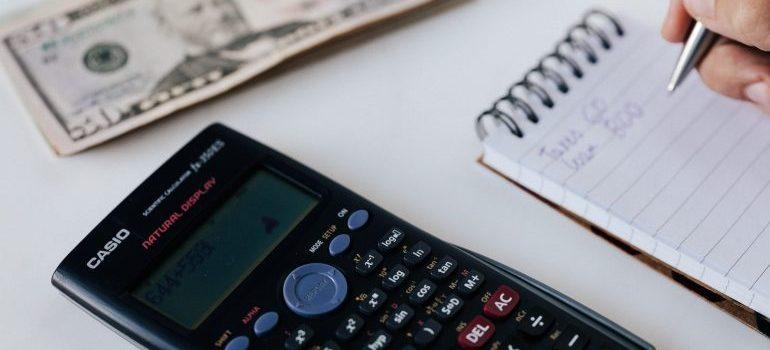 Notebook, calculator and a dollar bill