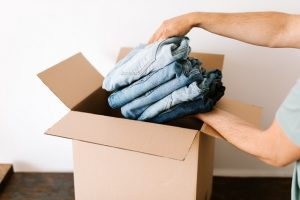 A person placing clothes into a moving box