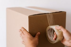 person sealing a box
