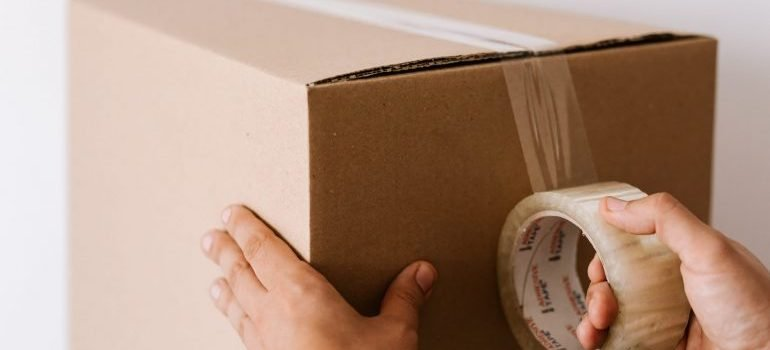 Sealing a cardboard box with tape