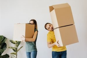 Cheerful couple carrying boxes with belongings