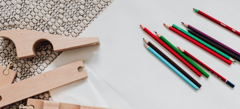 a disassembled toy and colorful pens- how to pack toys for moving