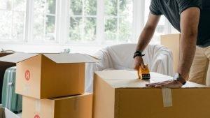 A man taping down a moving box