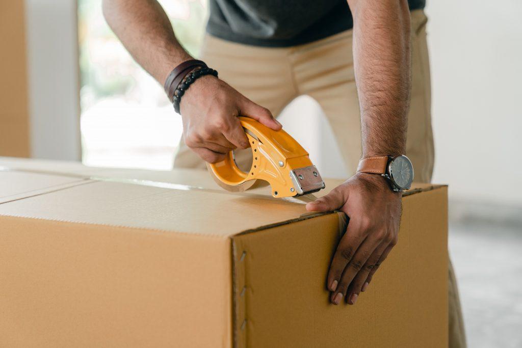 A packer sealing a box shut.
