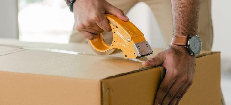 male sealing a moving box with a packing tape
