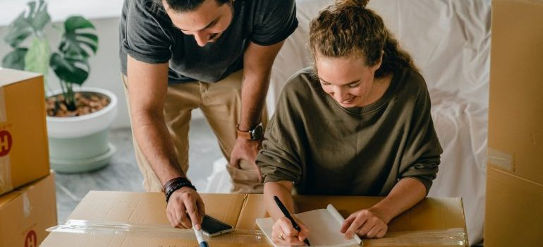 Couple writing in notebook near boxes before relocation