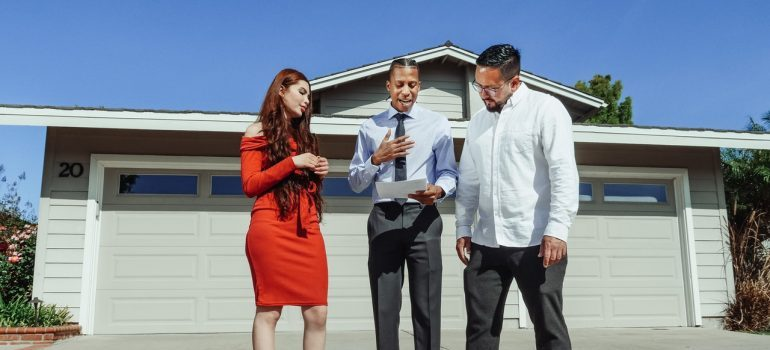 Three persons standing in front of a home that is for sale.