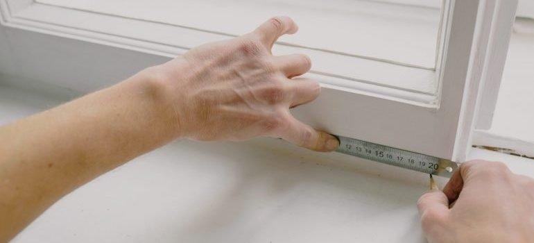 A person measuring window dimensions
