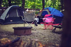two tents and two camp chairs in the forest