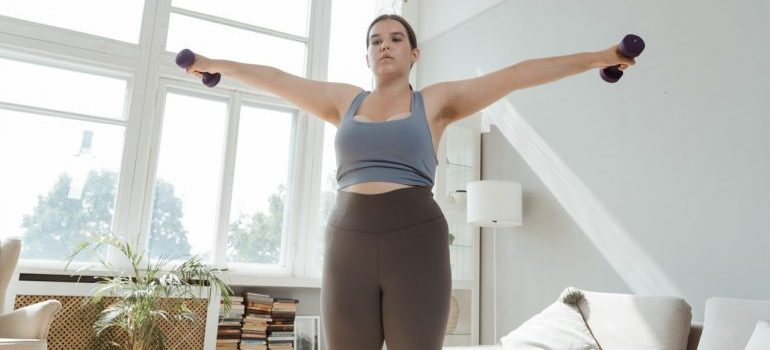 Woman exercising with two dumpbells