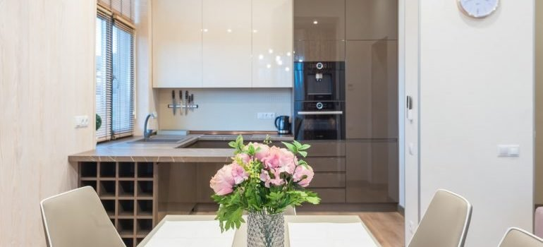 Tidy and clean kitchen and dining room with a vase with flowers on the table.
